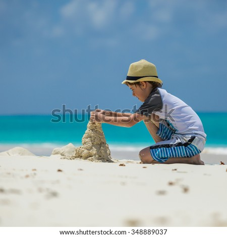 Little boy making sand castle at the beach - stock photo