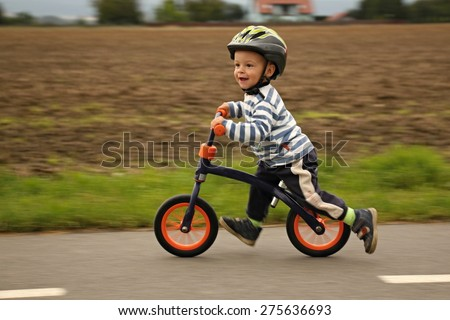 Little boy on a bicycle. Caught in motion, on a driveway (motion blurred). Preschool child's first day on the bike. The joy of movement. Little athlete learns to keep balance while riding a bicycle. - stock photo