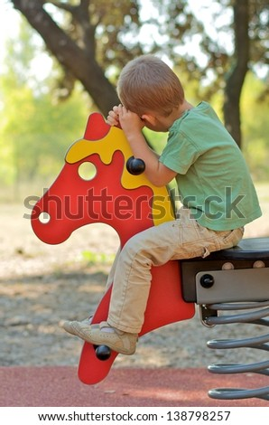 little boy on a horse on a playground - stock photo