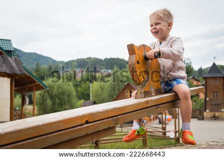 Little boy on a wooden swing - horses. Kid playing in the street. Kid playing in the mountain resort. Childrens games, fun, kid - the concept of childhood. - stock photo