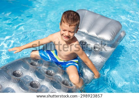 Little boy on air mattress in pool - stock photo