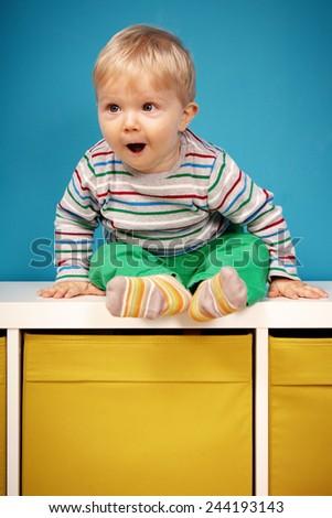 Little boy on cabinet - stock photo