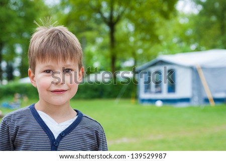 Little boy on camping park with tent in background - stock photo