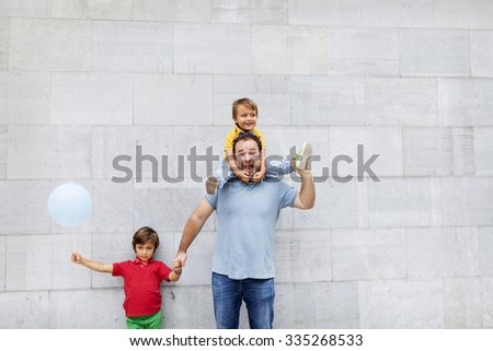 little boy on dad shoulders - stock photo