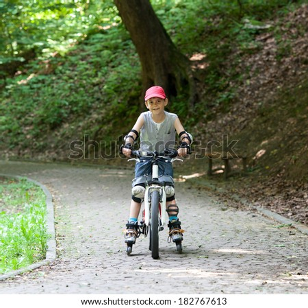 Little boy on roller skates and bike simultaneously - stock photo