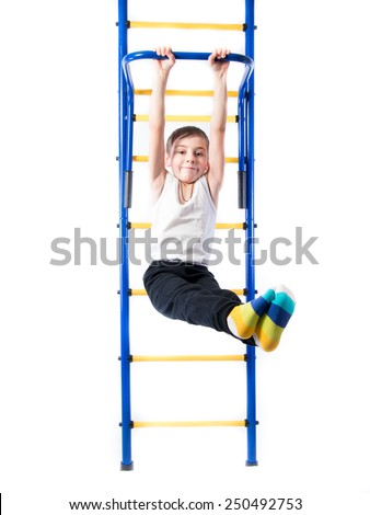 Little boy on the bar whist legs outstretched and smiling on a white background - stock photo