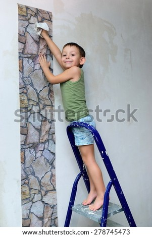 Little boy on the stairs smoothes wallpaper - stock photo