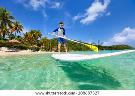 Little boy on tropical beach vacation paddling on stand up board - stock photo