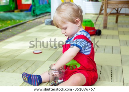 Little boy one year old playing with colorful marbles outdoors in summer. Happy kid having fun. Creative leisure with toddlers. - stock photo