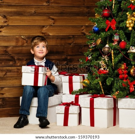 LIttle boy opening gift box under christmas tree in wooden house interior  - stock photo