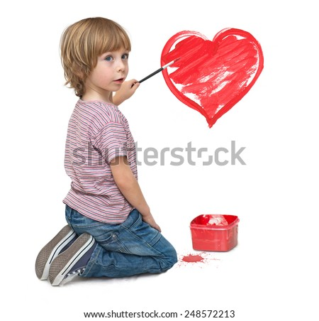 Little boy painting a red heart on the wall   - stock photo