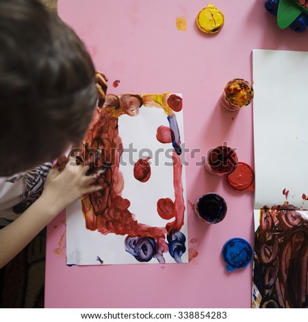 Little boy painting with his hands - stock photo