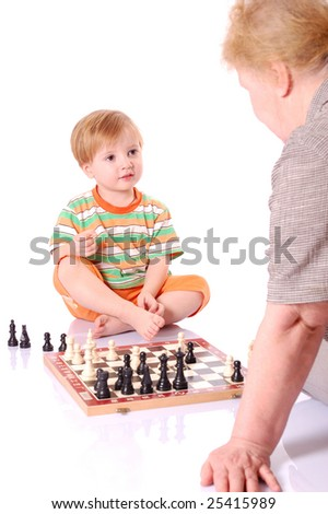 Little boy play chess with his grandmother on the ground. - stock photo