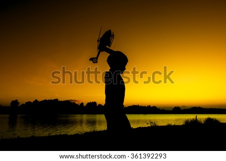 little boy play helicopter toy at river sunset background - stock photo