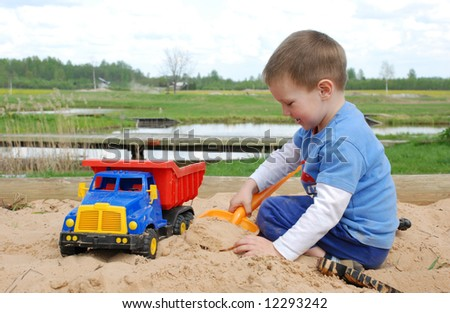 Little boy play in the sand box with color toy car - stock photo