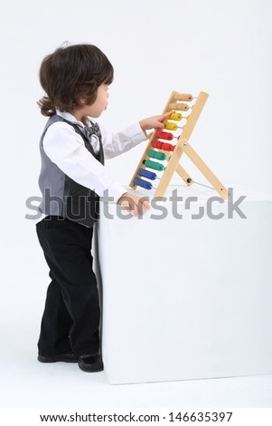 Little boy play with colorful abacus on big white cube in studio. - stock photo