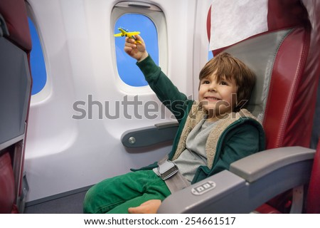 Little boy play with toy plane flying to vacation - stock photo