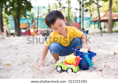 Little boy playing at playground with sand and color toy - stock photo