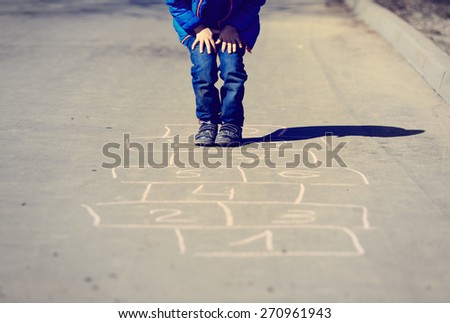 little boy playing hopscotch on driveway outside - stock photo