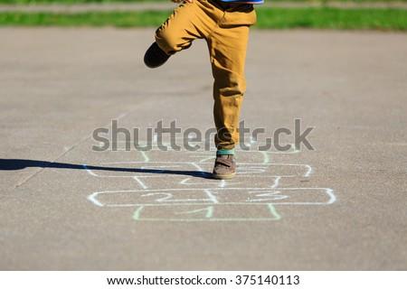 little boy playing hopscotch on playground - stock photo