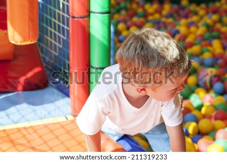 Little boy playing in colorful balls park playground - stock photo