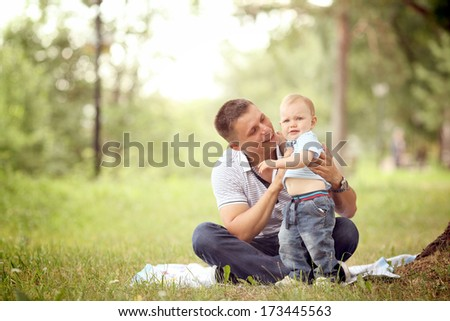 little boy playing in the park with dad - stock photo