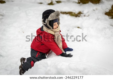Little boy playing in the snow - stock photo