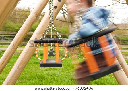 Little boy playing on a swing - stock photo