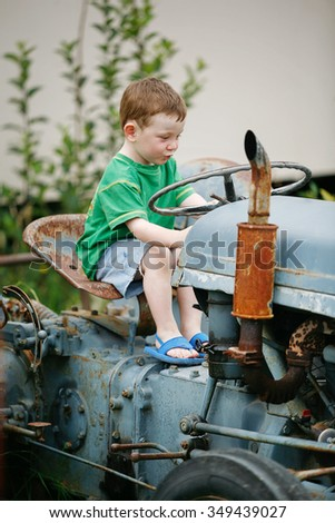 Little boy playing on an old abandoned tractor - stock photo