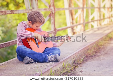 Little boy playing on his guitar - stock photo