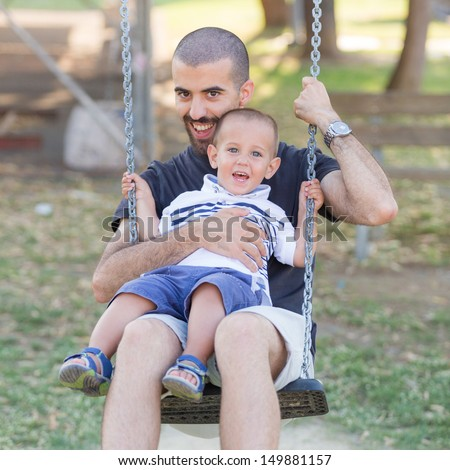 Little Boy Playing on the Swing with Father or Uncle - stock photo