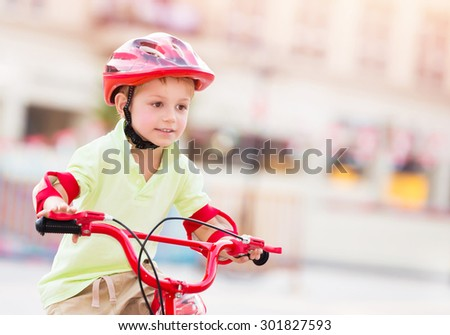 Little boy playing outdoors, cute cheerful child having fun in summer camp, nice kid riding on red stylish bicycle on blur urban background, enjoying carefree summer holidays  - stock photo