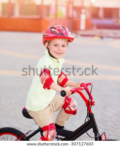 Little boy playing outdoors, cute cheerful child having fun in summer camp, riding on red stylish bicycle, enjoying carefree summer holidays  - stock photo