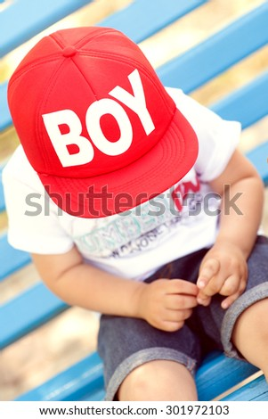 Little boy playing outdoors in the city in park looking down and covering his face by the cap - stock photo
