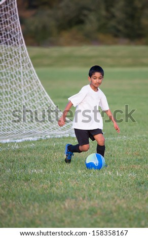 Little Boy Playing Soccer - stock photo