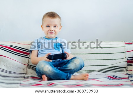 Little boy playing video games at home - stock photo