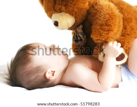Little boy playing with a bear - stock photo