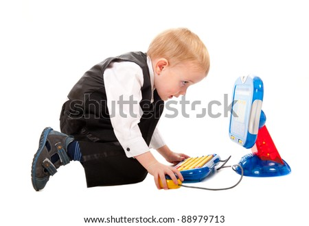 Little boy playing with a toy computer isolated on white - stock photo
