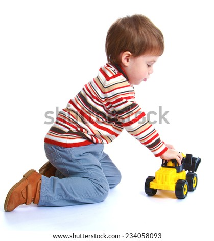 Little boy playing with a toy excavator .Isolated on white background. - stock photo