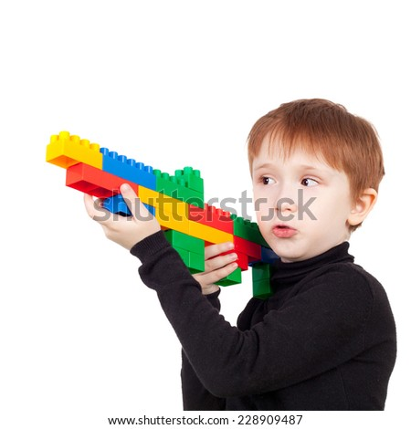 little boy playing with bricks making the pistol - stock photo