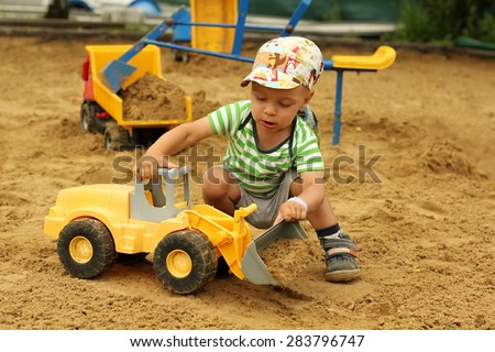 Little boy playing with children excavator in the sandbox. - stock photo