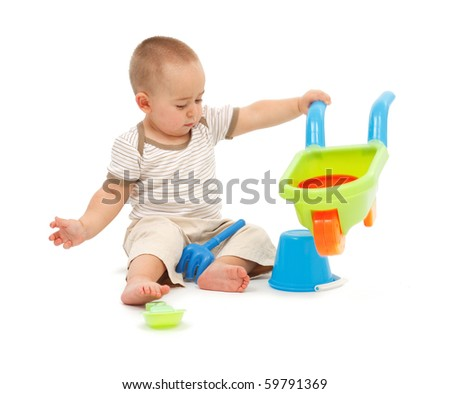 Little boy playing with colorful plastic beach toys - stock photo