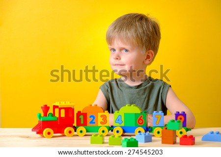 Little boy playing with colorful plastic blocks with numbers. - stock photo