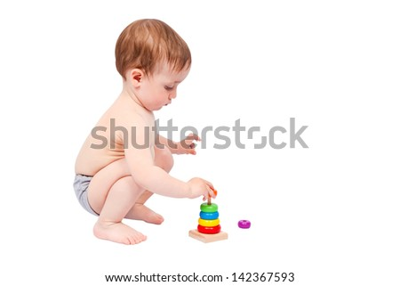 Little boy playing with colorful pyramid isolated on white background - stock photo