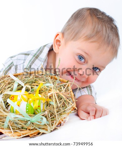 Little boy playing with easter eggs in basket - stock photo