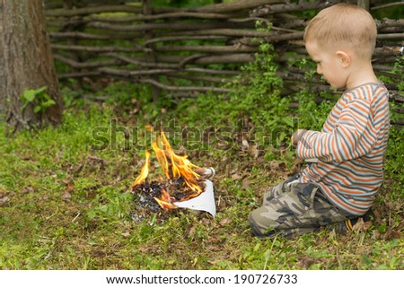 Little boy playing with fire squatting down on the ground in front of a pile of burning twigs and leaves, side view - stock photo