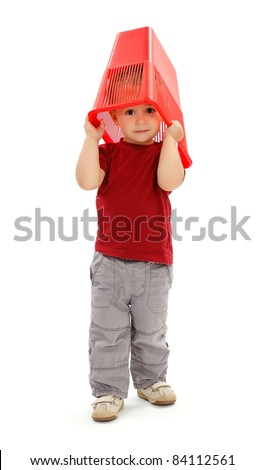 Little boy playing with garbage bin, pulling on his head - stock photo