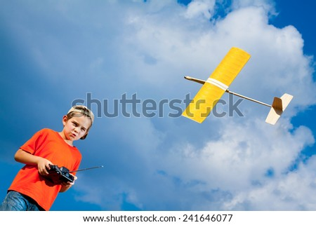 Little boy playing with handmade RC airplane toy - stock photo