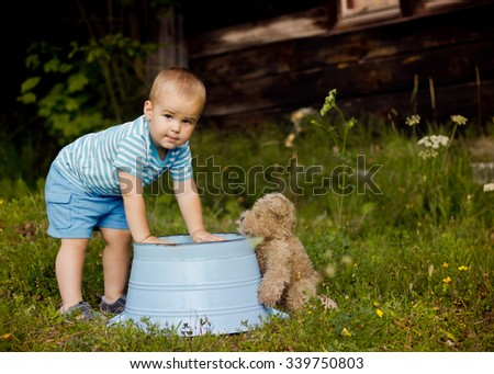 Little boy playing with his friend teddy bear outdoors - stock photo