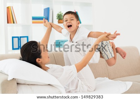Little boy playing with his mother at home - stock photo